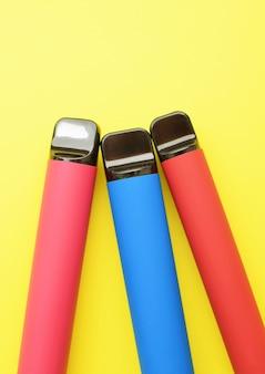 Три электронные сигареты на желтом фоне. место для вашего текста.