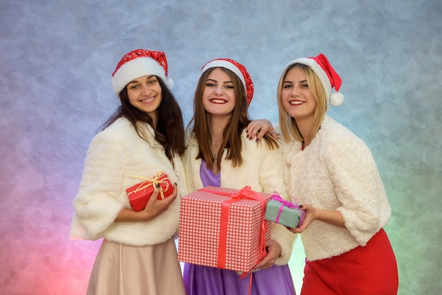 Three elegant women with gift boxes. happy new year celebration