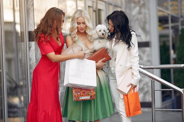街で買い物袋を持つ3つのエレガントな女性