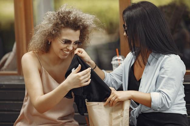 都市のショッピングバッグを持つ3つのエレガントな女性