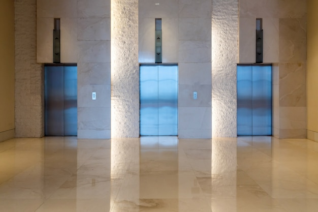 Three elevator doors interior building with low light
