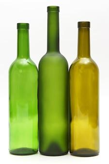 白い背景の上のワインの3つの空のボトル。飲用器具