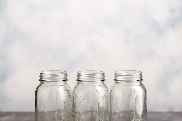 Three empty clean canning jars with drops of water. three empty clean canning jars with drops of water.
