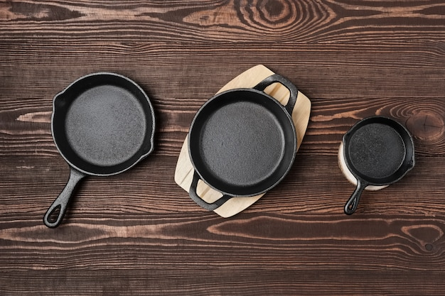 Three empty mini cast-iron skillets on wooden table, view from above