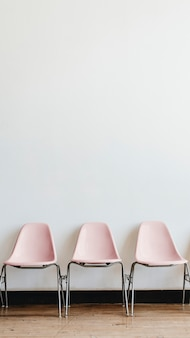 Three empty pastel pink chairs in a room