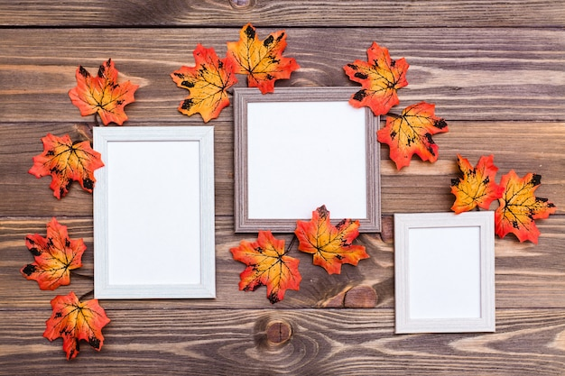 Three empty photo frame on a brown wooden table surrounded by orange maple leaves.