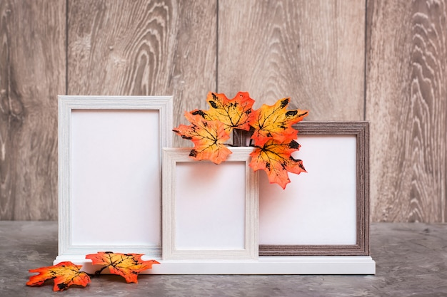 Three empty photo frames on a stand and orange maple leaves stand on a table. white-orange-beige color scheme. copy space