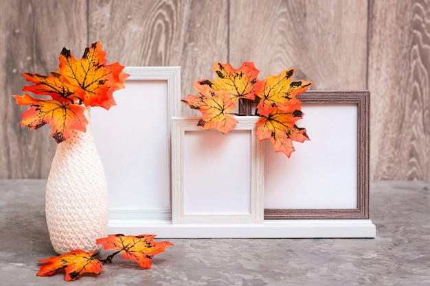 Three empty photo frames on a stand and a vase with orange maple leaves stand on the table. white-orange-beige color scheme. copy space