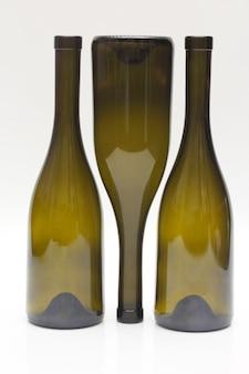 Three empty wine bottles close up on white