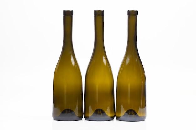 Three empty wine bottles on white