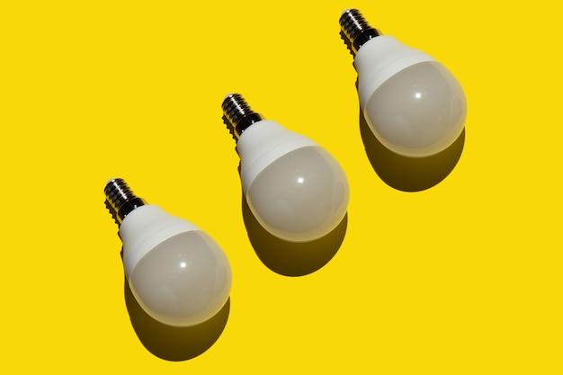Three energy saving light bulbs on a yellow background