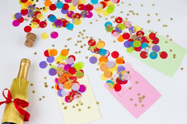 Three envelopes on a white background, colored confetti are flying from them, a bottle of champagne