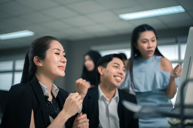 Трое возбужденных сотрудников читают хорошие новости онлайн на рабочем столе компьютера в офисе