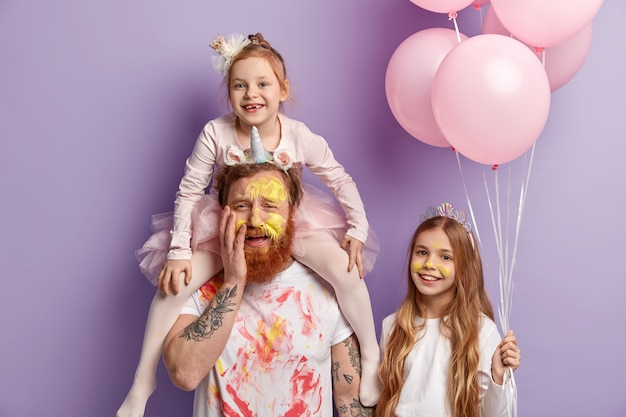 Three family members pose indoor over purple wall. funny two daughters and dad have fun, color faces with colorful watercolors, celebrate childrens day together. entertainment concept.