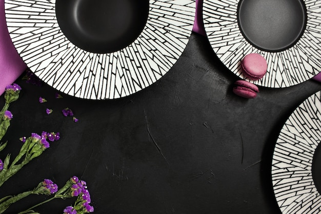 Three fancy plates on black background. creative restaurant table setting with flowers and purple color accents
