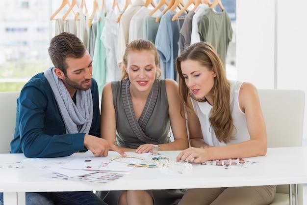 Three fashion designers discussing designs