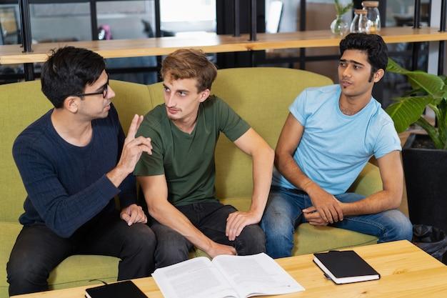 Tre compagni di studio che studiano e discutono i compiti