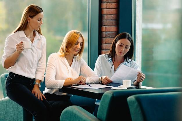 現代のオフィスでコーヒーを飲みながらビジネスプロジェクトに一緒に取り組んでいる3人の女性従業員。チームワークの概念。