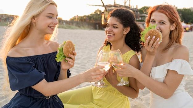 一緒にビーチでハンバーガーを食べる3人の女性の友人