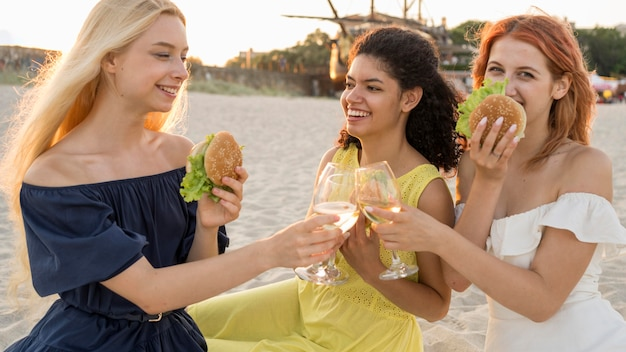 Three female friends eating burgers at the beach together