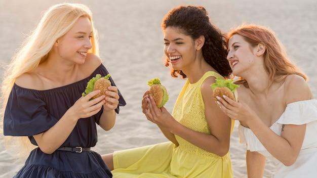 Три подруги вместе наслаждаются гамбургерами на пляже