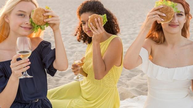 ビーチでハンバーガーを一緒に楽しむ3人の女性の友人