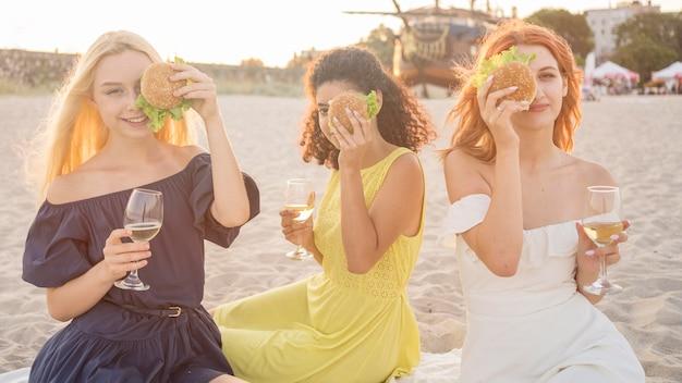 ビーチでハンバーガーを楽しんでいる3人の女性の友人