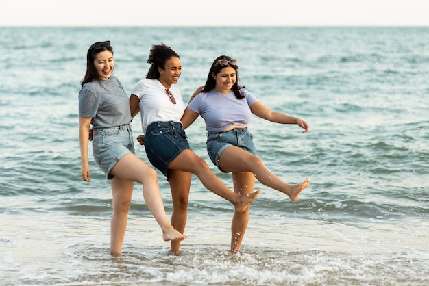 ビーチで一緒に楽しんでいる3人の女性の友人