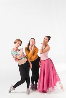 Three female friends posing against white backdrop