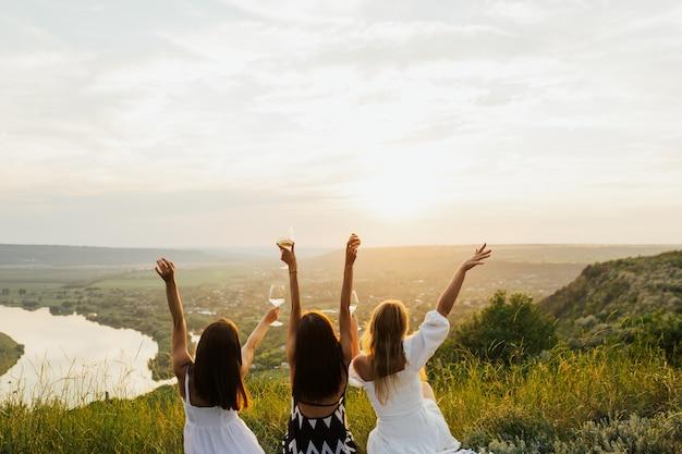 丘の上の芝生に座って楽しんでいる3人の女性の友人。