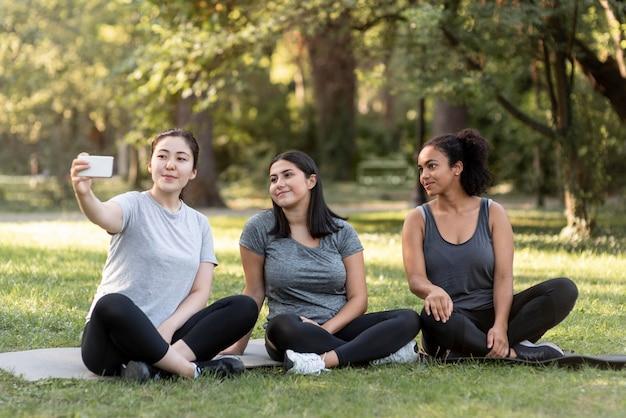 公園で自分撮りをしている3人の女性の友人