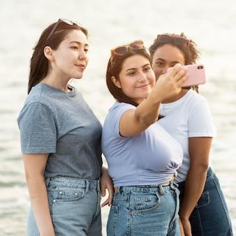 Три подруги, делающие селфи на пляже
