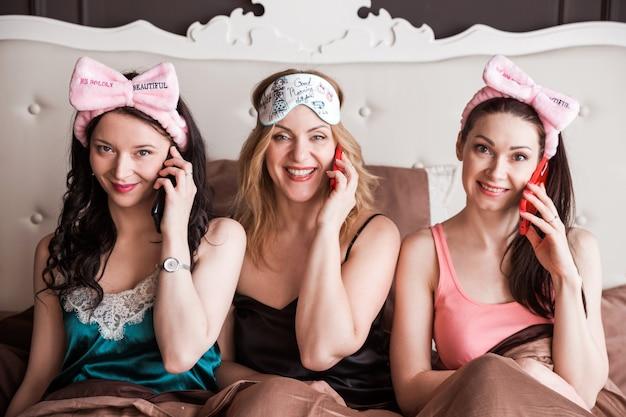 Три подруги устроили пижамную вечеринку на шикарной кровати. девушки сидят на кровати, разговаривают по телефону и улыбаются.