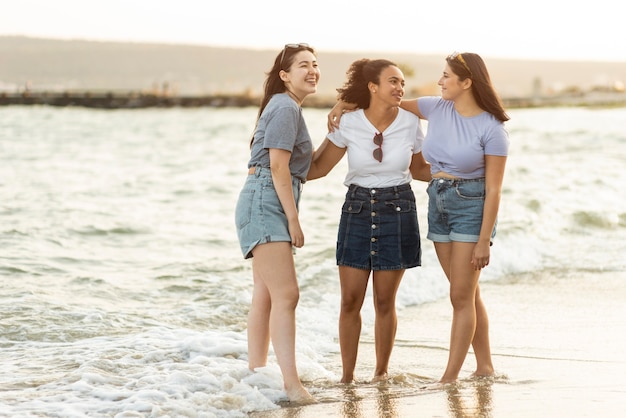 Three female friends together on the beach