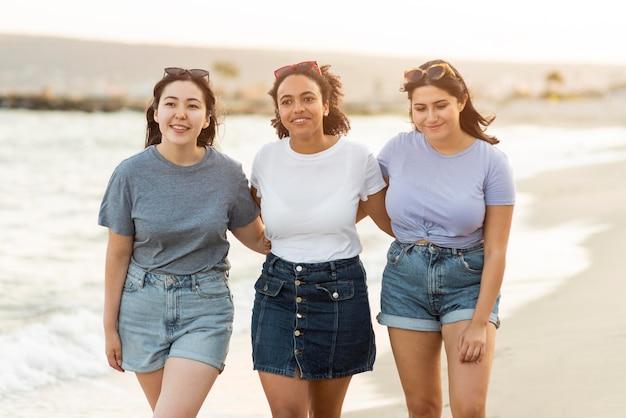 Three female friends walking on the beach