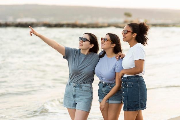 ビーチの景色を眺めるサングラスをかけた3人の女性の友人