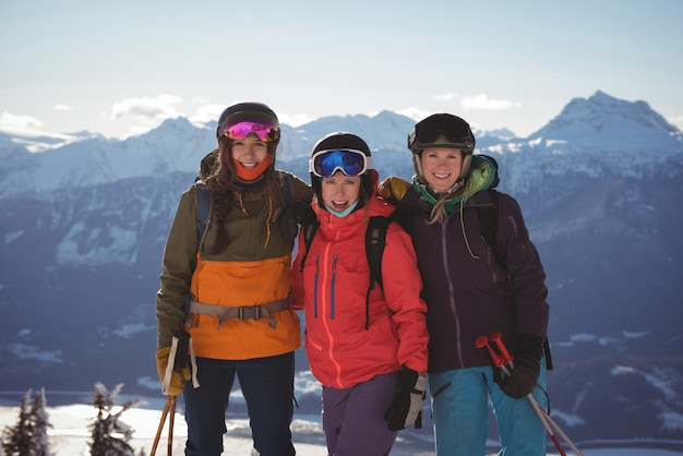 Three female skiers standing together on snow covered mountain