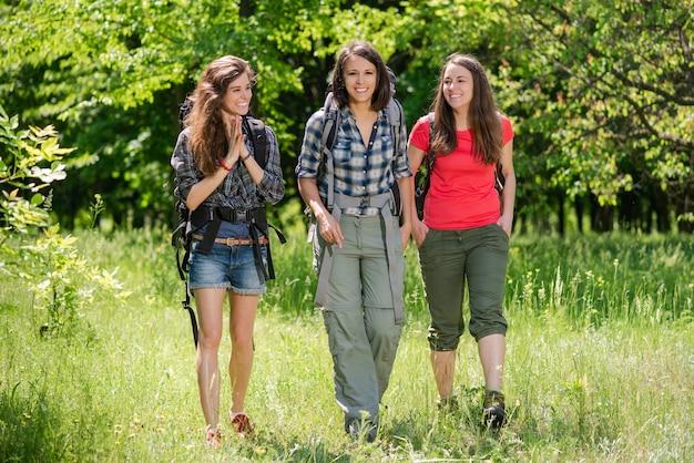 Три туристки с женской улыбкой гуляют с рюкзаками