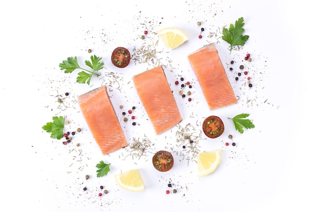白い背景の上のスパイスと芳香性のハーブと新鮮な生鮭魚の3枚の切り身。フラットレイ。