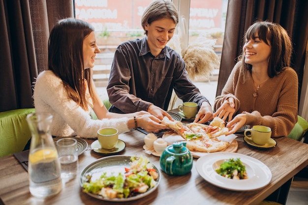 Three firends together eating pizza in a cafe