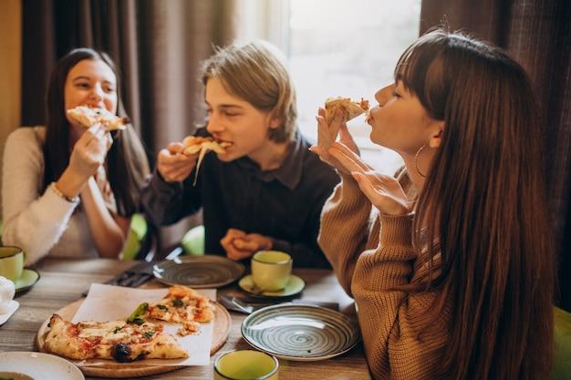 카페에서 피자를 먹고있는 세 명의 친구들