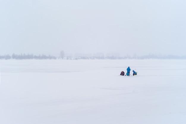 遠くにいる3人の漁師が霧の雪に覆われた冬の風景の中で氷釣りをします