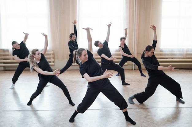 Three fit girls and four guys in black activewear standing on the floor with outstretched legs and bent knees while exercising in dance studio