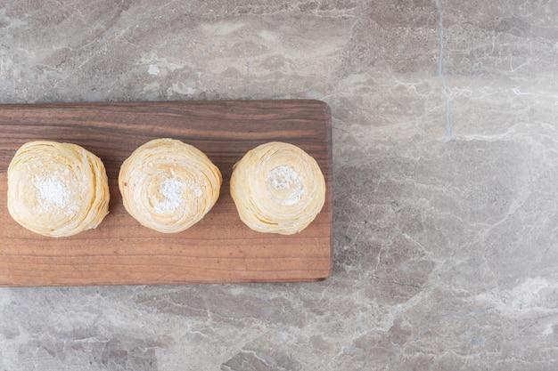Tre biscotti a scaglie su una tavola su una superficie di marmo