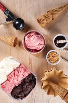 Three flavors of ice cream in a delivery container, making a composition with a strawberry ice cream container and several cones. top view