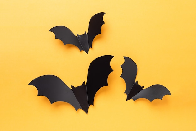 노란색과 흰색 배경에 세 개의 비행 검은 종이 박쥐. 할로윈 개념입니다. 평면 위치, 복사 공간 - 이미지