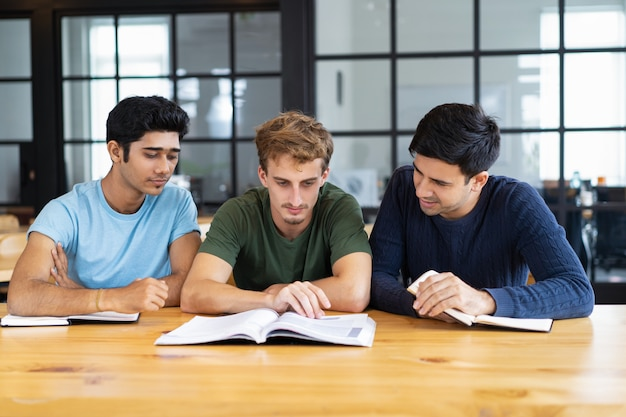 Three focused students reading textbooks together at desk