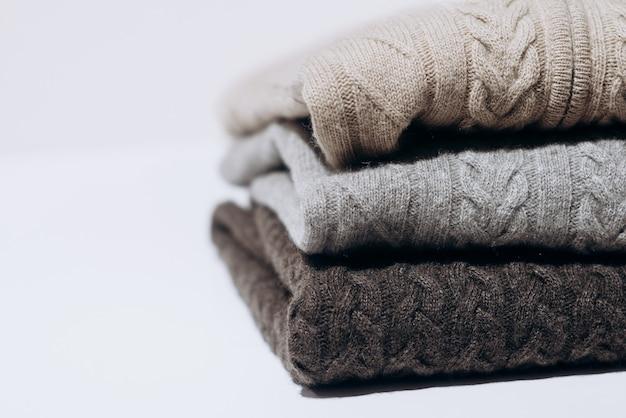 흰색 배경에 다양한 회색 음영으로 된 세 개의 접힌 캐시미어 니트 스웨터. 세 가지 회색 음영. 검은 배경에 고립 된 세 스웨터의 스택입니다. 니트 울 스웨터.