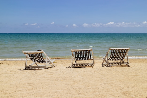 Three folding chairs on the beach with sea and bright sky in the background at koh mak in trat