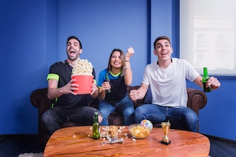 Three football fans celebrating in living room